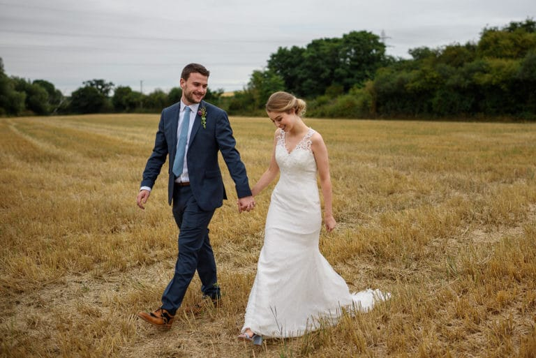 bride and groom walking through a field - norwich wedding photographer